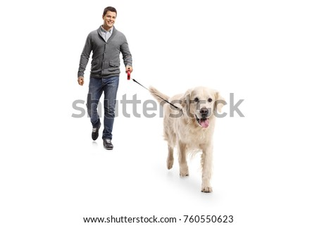 Full length portrait of a young man walking a dog isolated on white background