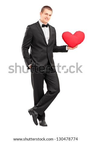 Full length portrait of a young man wearing black suit and holding a red heart isolated on white background - stock photo