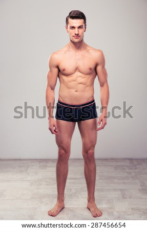 Full length portrait of a young muscular man standing in studio - stock photo
