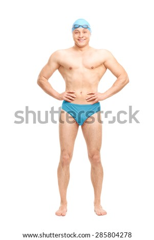 Full length portrait of a young muscular swimmer with a blue swim cap and black goggles isolated on white background - stock photo