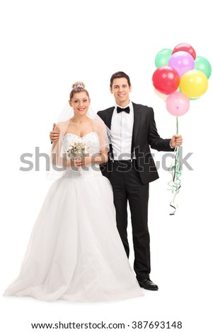 Full length portrait of a young newlywed couple holding a bunch of balloons and posing together isolated on white background - stock photo