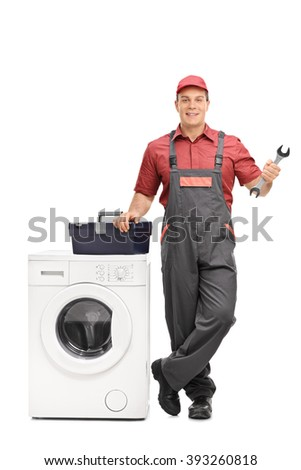 Full length portrait of a young repairman holding a wrench and standing next to a washing machine isolated on white background - stock photo