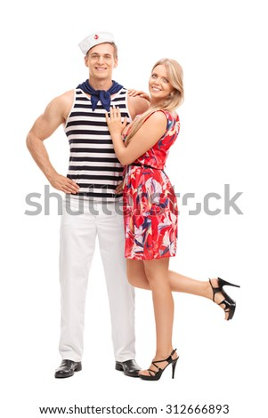 Full length portrait of a young sailor hugging his girlfriend and looking at the camera isolated on white background