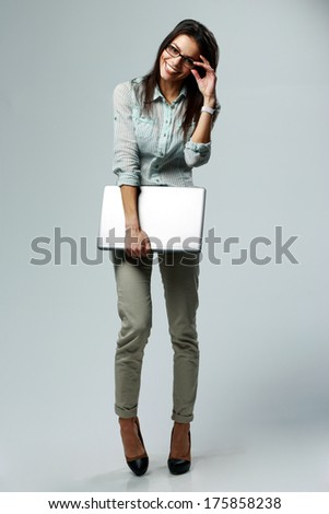Full-length portrait of a young smiling businesswoman holding laptop on gray background - stock photo