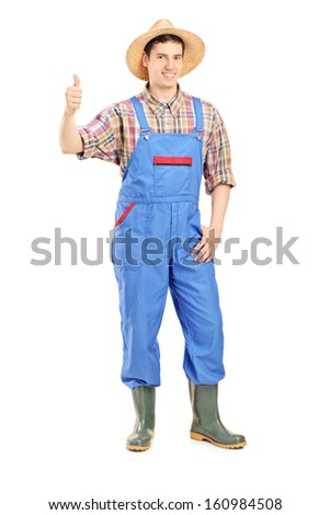 Full length portrait of a young smiling farmer giving a thumb up isolated on white background - stock photo