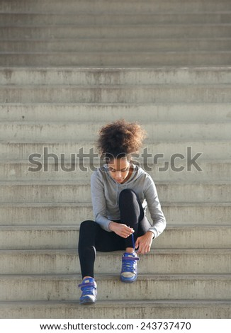 Full length portrait of a young sports woman tying shoelaces on steps