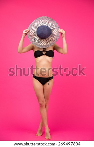 Full length portrait of a young woman in bikini covering her face with hat - stock photo
