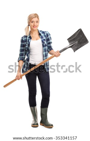 Full length portrait of a young woman in blue checkered shirt and gray rubber boots holding a shovel isolated on white background