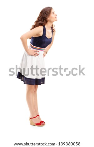 Full length portrait of a young woman in profile looking upwards, isolated on white background - stock photo