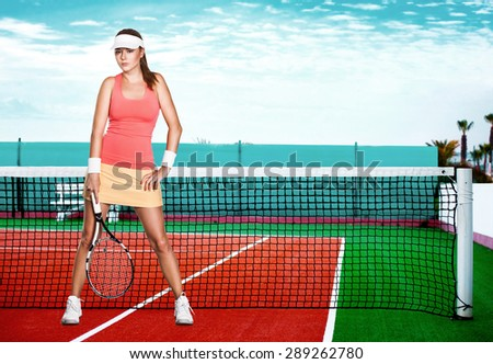 Full length portrait of a young woman on a tennis  dross field - stock photo