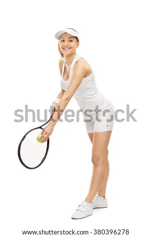Full length portrait of a young woman playing tennis and smiling isolated on white background - stock photo