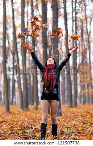 Full length portrait of a young woman playing with dried leaves in the woods - stock photo