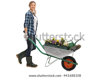 Full length portrait of a young woman pushing a wheelbarrow with gardening equipment isolated on white background - stock photo