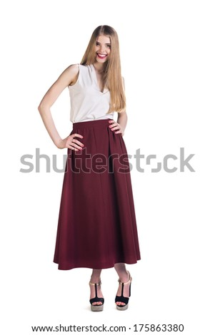 Full length portrait of a young woman, shot on white background. she looks over her shoulder, straight to the camera. - stock photo