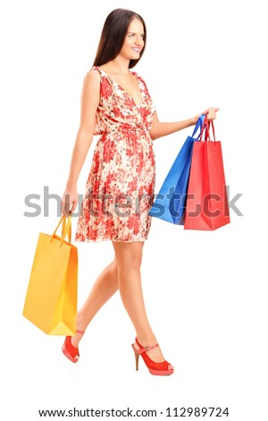 Full length portrait of a young woman walking with shopping bags isolated on white background