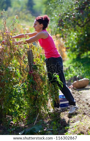 Full length portrait of a young woman working in her garden