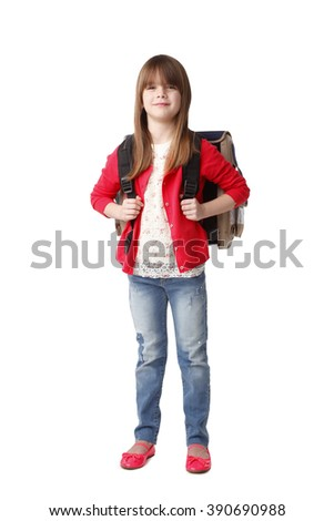 Full length portrait of adorable preschool girl with backpack looking at camera and smiling while standing against white background.
