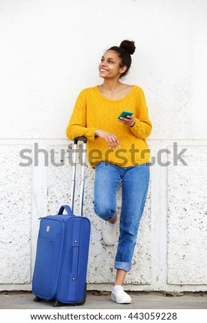 Full length portrait of african american female traveler standing outside with suitcase and mobile phone - stock photo