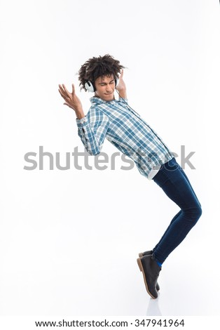 Full length portrait of afro american man with headphones dancing isolated on a white background - stock photo