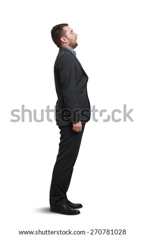 full-length portrait of amazed man in black suit looking up with open mouth. isolated on white background  - stock photo