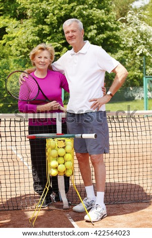Full length portrait of  an active senior couple standing at tennis court and ready to play tennis.