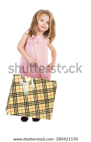 Full length portrait of an adorable little girl with pink dress carrying a shopping bag over white background - stock photo