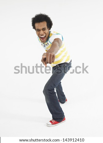 Full length portrait of an Afro man pointing at you against white background - stock photo