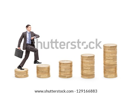 Full length portrait of an ambitious businessman with a briefcase walking over piles of coins isolated on white background