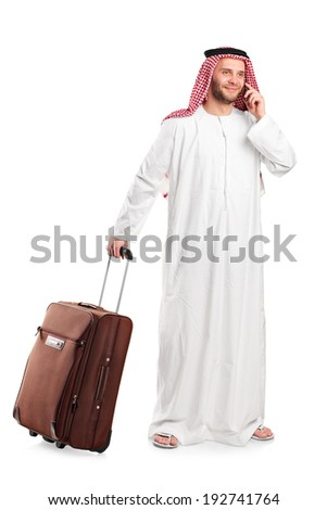 Full length portrait of an Arabic sheik talking on phone and carrying a luggage isolated on white background