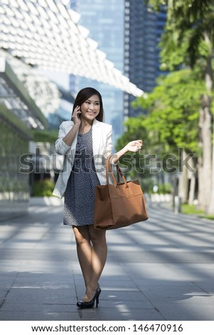 Full length Portrait of an Asian Businesswoman using a smart phone and walking in the street.