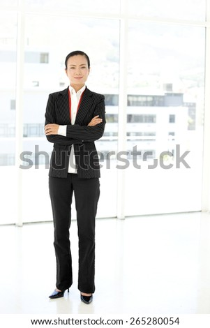Full length portrait of an Asian Businesswoman with arms crossed - stock photo