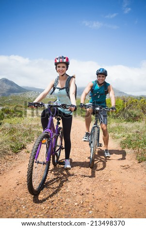 Full length portrait of an athletic couple mountain biking