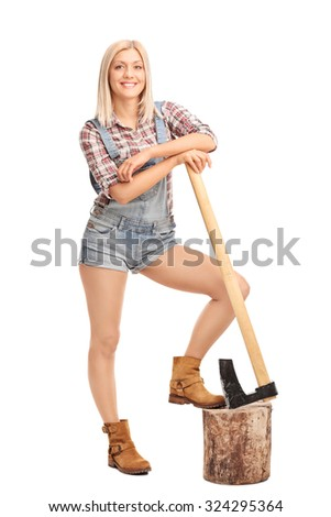 Full length portrait of an attractive blond woman in short jumpsuit leaning on an axe and looking at the camera isolated on white background