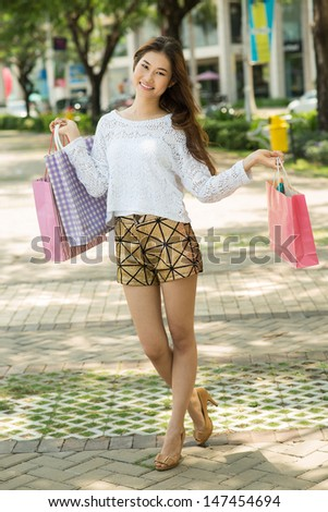Full-length portrait of an attractive lady with shopping bags outside