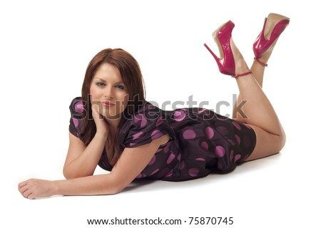Full length portrait of an attractive model lying down in a party dress isolated on white