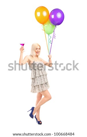 Full length portrait of an attractive woman holding balloons and cocktail isolated on white background