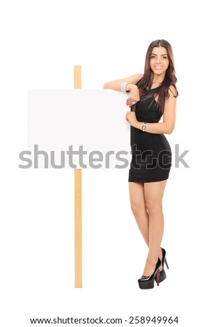 Full length portrait of an attractive woman standing next to blank signboard isolated on white background - stock photo