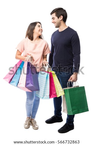 Full length portrait of an attractive young couple carrying shopping bags in a studio