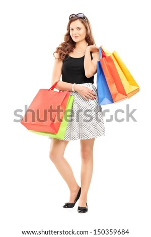Full length portrait of an attractive young woman posing with shopping bags isolated on white background - stock photo