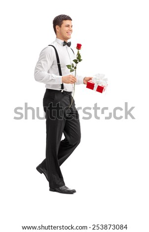 Full length portrait of an elegant guy walking with a rose and a present isolated on white background - stock photo