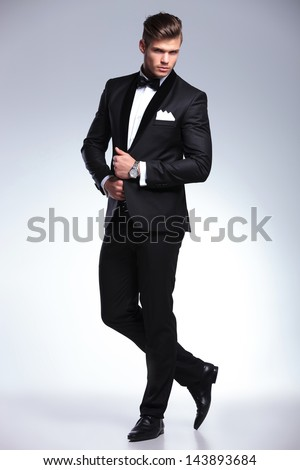 full length portrait of an elegant young fashion man in tuxedo looking at the camera while holding his hands on his jacket and a leg behind the other. on gray background - stock photo