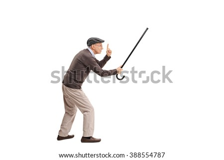 Full length portrait of an enraged senior man holding his cane as a sword and threatening someone isolated on white background