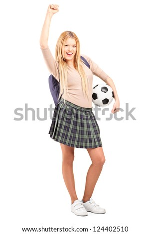 Full length portrait of an euphoric female student with backpack holding a soccer ball isolated on white background - stock photo