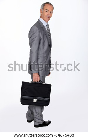 Full length portrait of an older businessman with a briefcase - stock photo