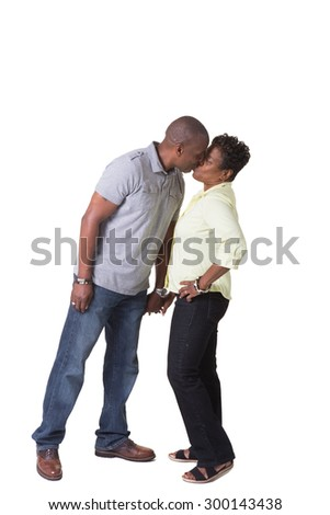 Full length portrait of an older couple kissing and holding hands, isolated - stock photo