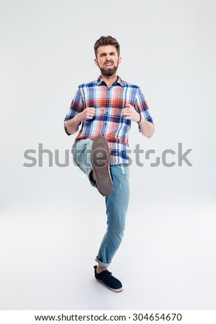 Full length portrait of angry man kicking isolated on a white background - stock photo