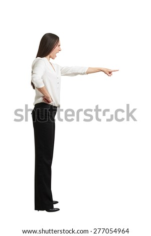 full length portrait of angry screaming woman in formal wear pointing finger at something. isolated on white background - stock photo