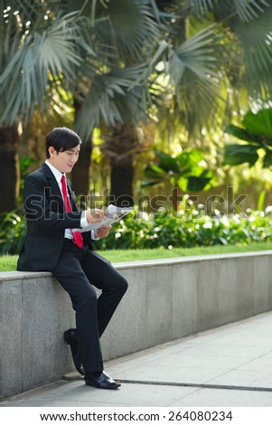 Full-length portrait of Asian businessman reading newspaper outdoors - stock photo