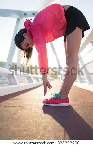 Full length portrait of athletic female dressed in bright sportswear stretching muscles before start evening run outside, young woman jogger in tracksuit workout out in summer during recreation time  - stock photo