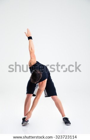 Full length portrait of athletic man doing stretching exercises isolated on a white background - stock photo